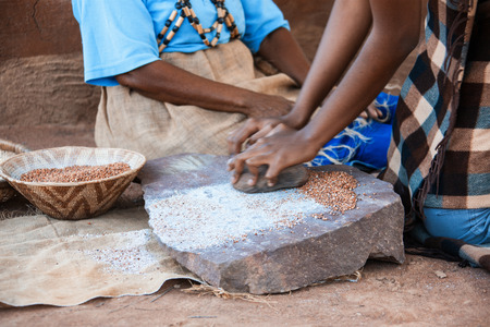 African woman in the village grinding traditionally some seeds