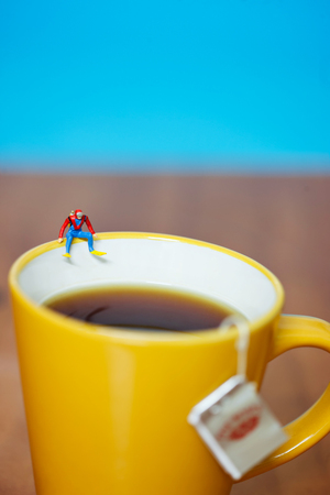 diver jumping in a cup of tea giant food concept