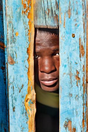 African child hiding behind a door in the village, Botswana