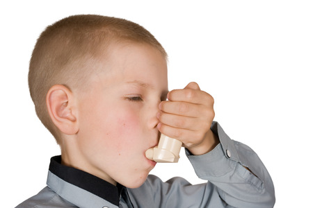 asthma: The boy injects an inhaler on an isolated background Stock Photo