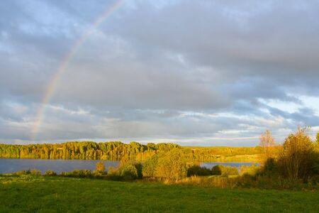The cloudy sky and autumn rainbow above lake photo