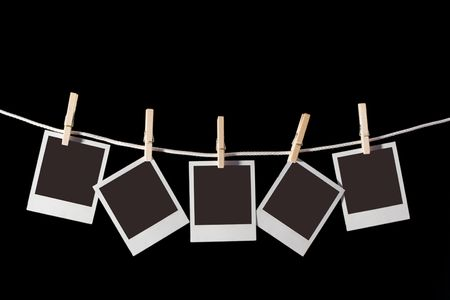Photos hanging on a cord, suspended by clothespins photo