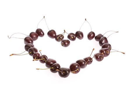 which: The berries of the sweet cherry which has been laid out in the form of heart