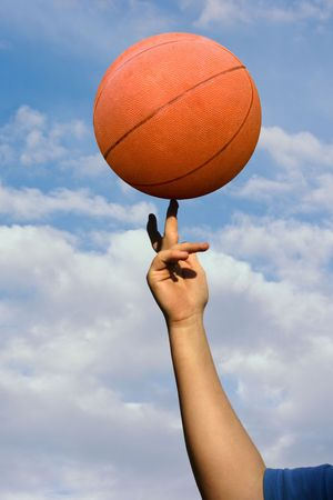 a basketball spinning on a finger with clouds in background