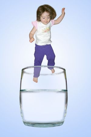 A little girle jumping into a glass of water