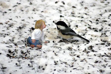 Een klein meisje met chatten met een mees