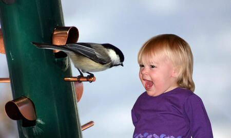 a little girl talking to a chickadee