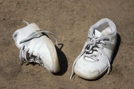 a pair of childrens shoes tossed in the dirt