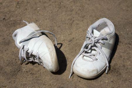 un par de zapatos para niños echados a la suciedad