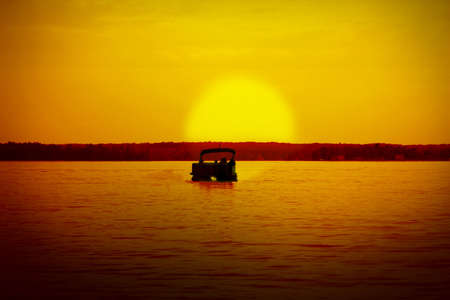 pontoon: a pontoon boat heading into the sunset Stock Photo