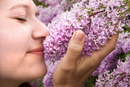 absorb: a lady enjoying the smell of some lilacs Stock Photo