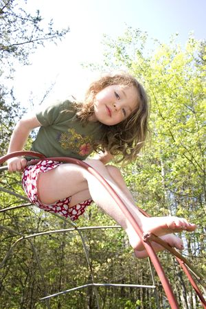 jungle gym: a little girl playing on a jungle gym Stock Photo
