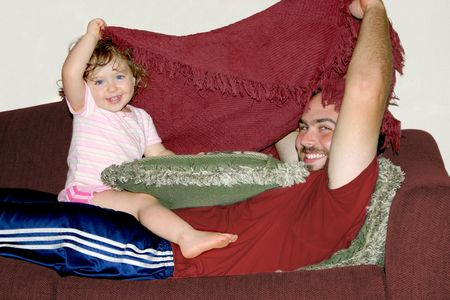 a father and daughter peeking from under a blanket photo
