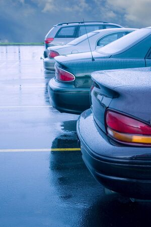 cars lined up in a rainy parking lot Stock Photo