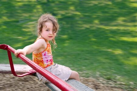 a little girl spinning on a merry-go-round Stock Photo