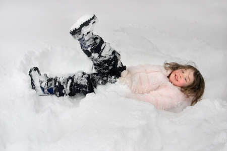 a little girl laying in the snow Stock Photo - 1282983