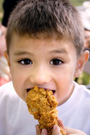 a latino boy eating a crispy chicken leg