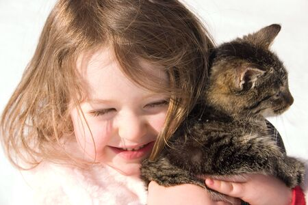 a little girl holding her pet kitty Stock Photo