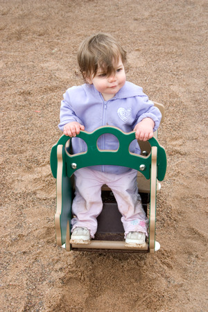 liesure: a little girl playing in a rocker in the park