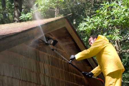 pressure: a man pressure washing a garage