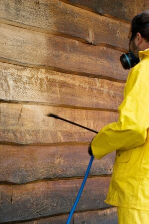 a man doing a chemical wash on the side of a garage Standard-Bild
