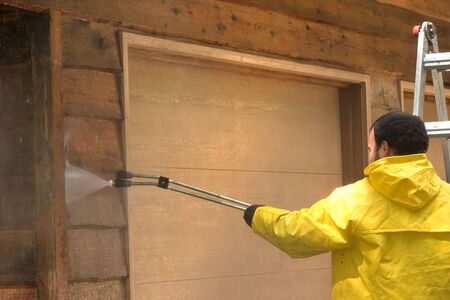 pressure: a man pressure washing a wood sided garage Stock Photo