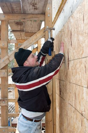 a man pounding a nail into the side of a building Stock Photo - 2466818