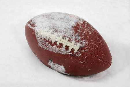 snow on the ground: a football covered with snow and laying in the snow