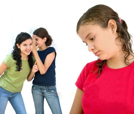 rumours: two young girls laughing behind another girls back Stock Photo