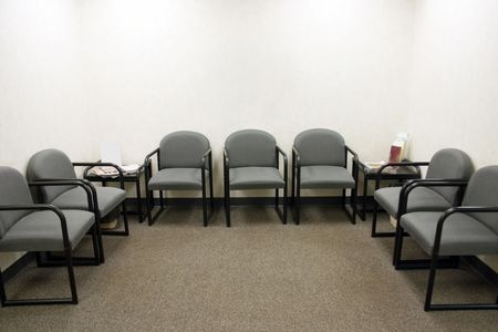 a ordinary waiting room with gray chairs
