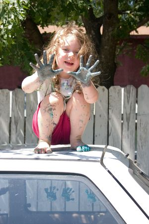 mess: a little girl with paint on her hand on top of a car