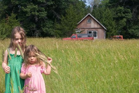 two little girls standing in a field in front of an old home