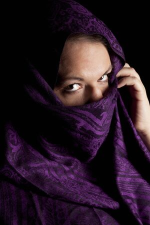 a mysterious woman behind a purple berka photo