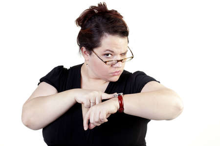 disapprove: A lady pointing at her watch with a scolding look Stock Photo