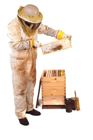 a beekeeper holding up a frame with honey and comb isolated