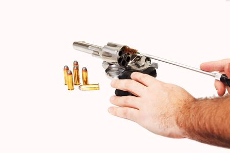 a man cleaning his pistol with bullets sitting next to it