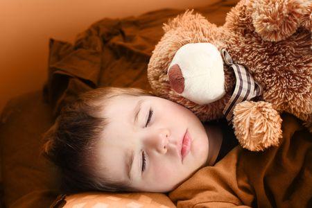a little boy sleeping with his teddy bear photo