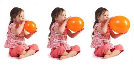 a little girl blowing up a balloon, isolated Stock Photo