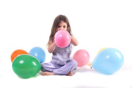 een klein meisje, een ballon omringd door ballonnen opblazen