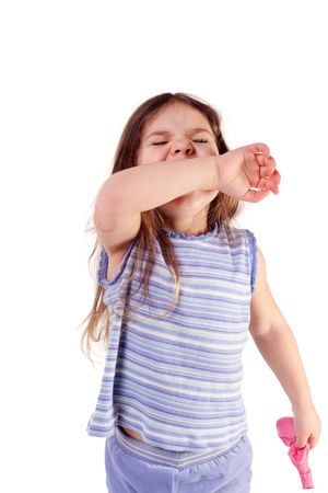 young girl sneezing into her arm, isolated Stock Photo