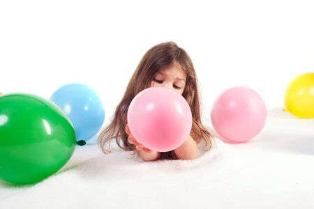 young girl blowing up a bunch of balloons