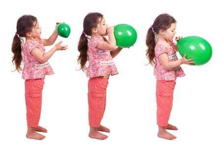 a pretty little girl blowing up a green balloon Imagens