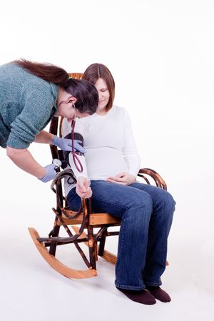 midwife taking the blood pressure of a pregnant lady photo