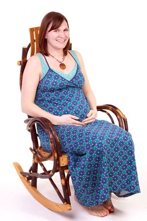 a pregnant mother sitting in a rocking chair photo