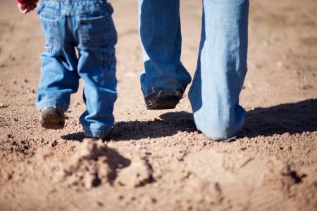Padre e hijo caminan juntos en la arena Foto de archivo