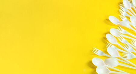isolated plastic forks and spoons on a yellow background Фото со стока