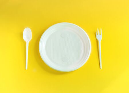 plastic spoon, fork and plate of white in the center and on a yellow background