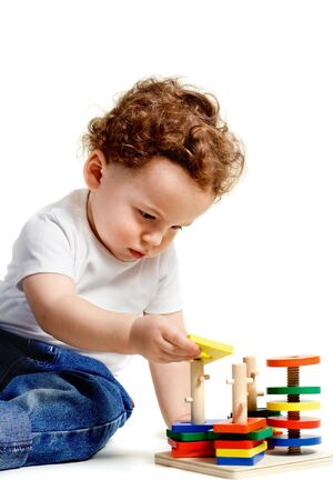 small boy sit and playing with colorful toys