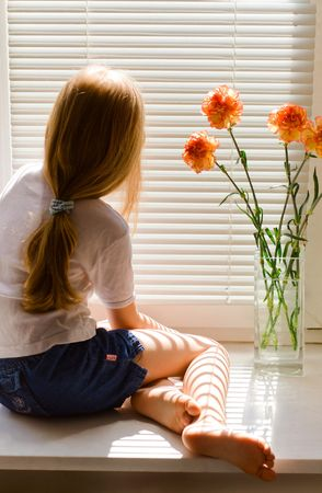 young blond girl sitting on a window-sill