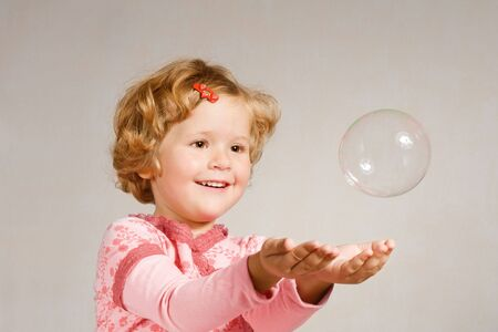 Small beautiful girl looking at a soap bubble